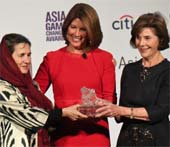 Afghan First Lady Rula Ghani (L) and former U.S. First Lady Laura Bush (R) present an Asia Game Changer award to Sherrie Weston (C), the executive vice president of Sesame Workshop. (Jamie Watts_Asia Society)