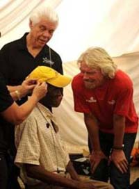 Sir Richard Branson observes as Bill Austin, Founder, Starkey Hearing Foundation, and his team of audiologists fit patients with hearing devices during the Foundation's first-ever hearing mission in Bushridge, Mpumalanga, South Africa