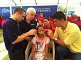Starkey Hearing Foundation So the World May Hear China (Chengdu) Mission - Young girl receives the gift of hearing as she is fitted with a hearing aid by David Shoemaker, CEO, NBA China (left); Bill Austin, Founder, Starkey Hearing Foundation (center left); Tani Austin, Founder, Starkey Hearing Foundation (center right); and NBA Legend Yao Ming (right)