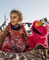 A young girl engages with Elmo at an informal tented settlement near Mafraq, Jordan, in February 2017. Photo courtesy of Sesame Workshop / Ryan Heffernan